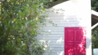 Shot of a Little House with White Wall and Red Door in the Garden video