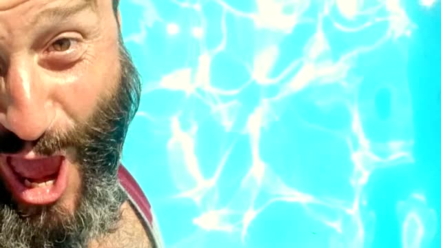 SELFIE shot of bearded man jumping into the pool video