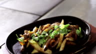 Shot of fryed vegetables with meat in hot pan on wooden stand video