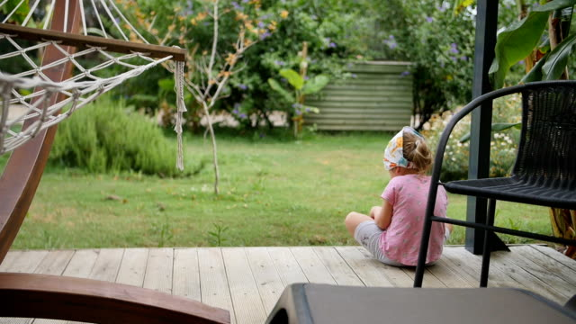 shot of little girl sitting at the backyard video