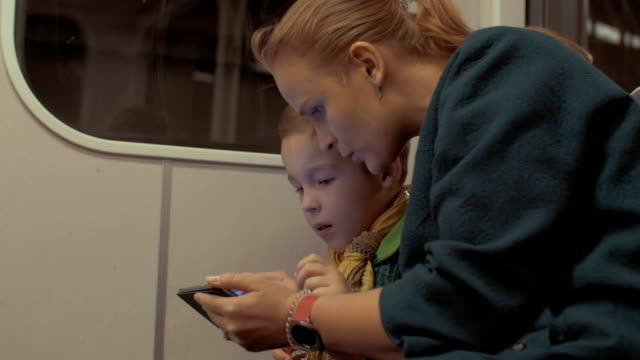 Shot of mother and son ride in the subway train using smartphone during trip, Prague, Czech Republic video