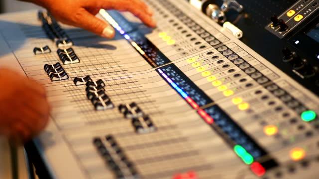 2 Shots Hand adjusting audio mixer control panel. video