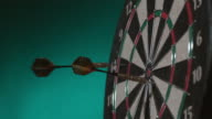 2 shots of darts hitting board in slow motion video