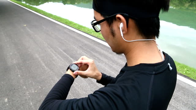 2 Shots of Man Using Heart Rate Monitor Watch for Running video