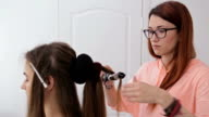 2 shots. Professional hairdresser doing hairstyle for young pretty woman video