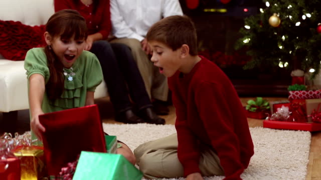 Siblings excited with opening presents on Christmas morning video