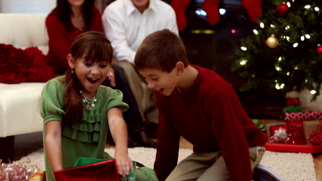 Siblings excitedly hug parents after opening present on Christmas morning video