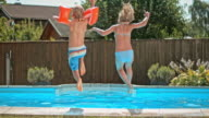 SLO MO DS Siblings holding hands and jumping into the pool on a sunny day video