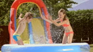SLO MO Siblings splashing each other with water in an inflatable pool video