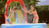 SLO MO Siblings splashing water in inflatable pool video