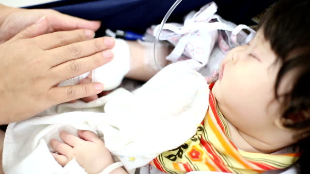 Sick baby receiving a saline on safety seat in hospital video