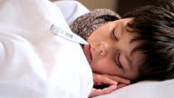 sick boy with digital thermometer video