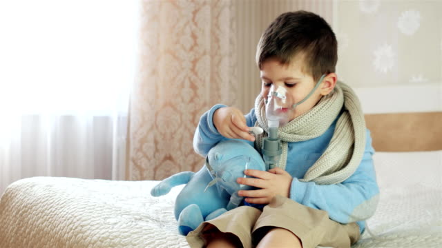 sick child breathes through nebulizer, baby does inhalation, boy with an oxygen mask on his face, treatment at home, medical procedure, Nebulizer video