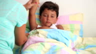 Sick child  lying in bed with a thermometer video