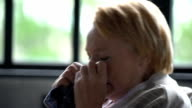 sick elderly woman much coughing and blowing nose into handkerchief video