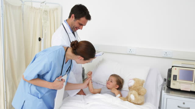 Sick girl lying in bed talking to nurse and doctor video