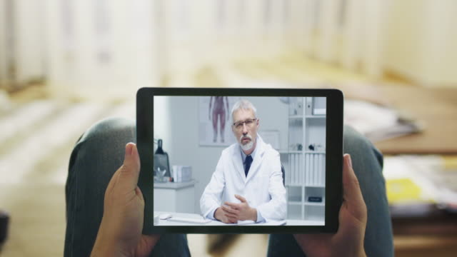 Sick Man Lying on a Couch and Having Video Conversation with His Doctor on a Tablet Computer. Point of View Shot. video