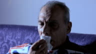 sick old man sitting on the sofa video