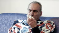sick old man with fever and cold: sitting on the sofa with blanket video