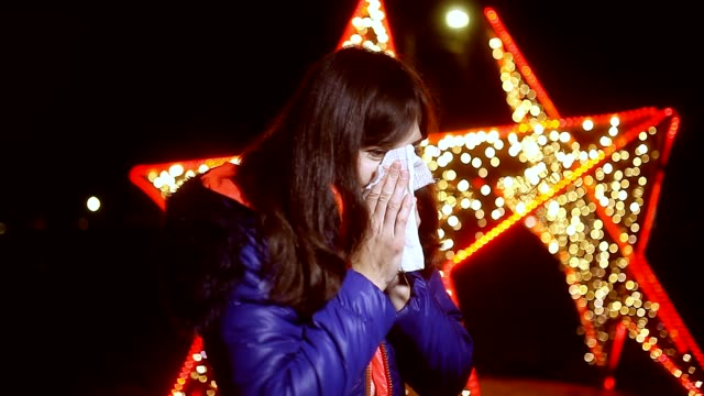 Sick woman blowing nose in paper tissue night Winter bokeh video