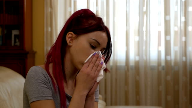 Sick young woman coughing and blowing her nose staying at home because the flu video