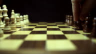 Side and wide angle shot of a chess board and the chess pieces lined up and a person is opening the game with a pawn video