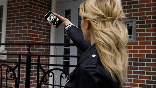 Side portrait of a beautiful blond girl using a smart phone to network, taking selfies pictures in a suburban home exterior, outdoors video