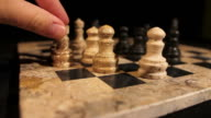 Side shot footage of a chess game and a person making the castling video