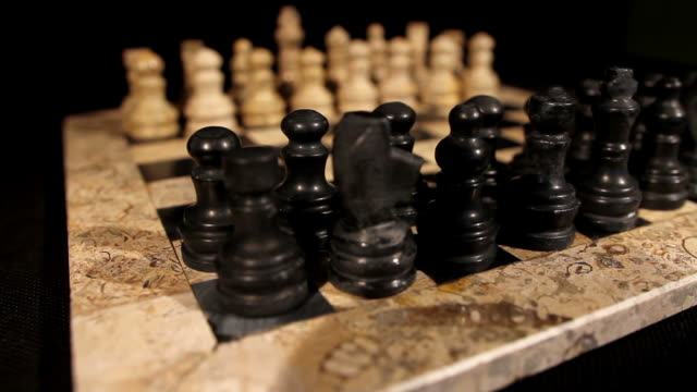 Side shot of a chess board with its pieces lined up, the focus goes from black to white pieces, and a person makes his first move with a pawn video