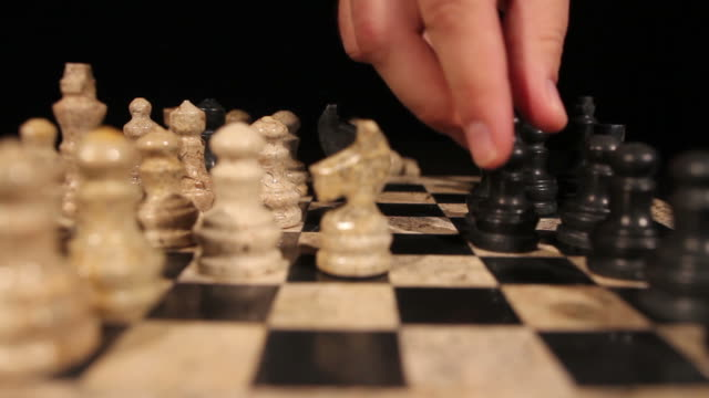 Side shot of a chess game, a black bishop takes a white pawn video