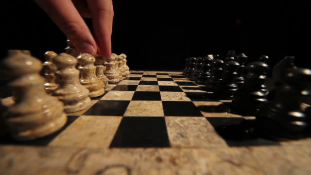 Side shot of a chess game start, a person plays his first move with a pawn video
