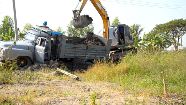 side view : Bulldozer dig soil from truck video
