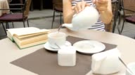 side view of a female pouring tea video