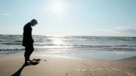 Side view of a young man standing barefoot on the beach on a lovely sunny day digging a hole in the sand with his toes video