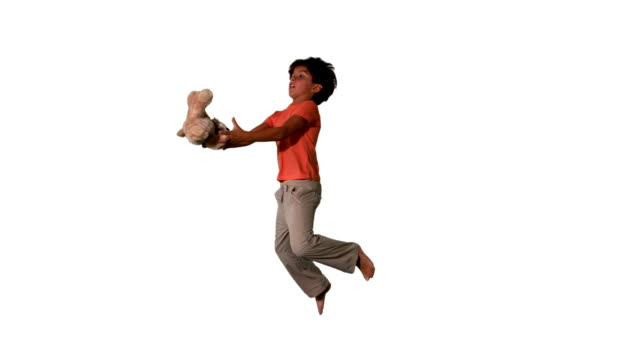 Side view of boy jumping up and catching teddy video