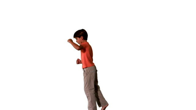 Side view of boy jumping up on white background video
