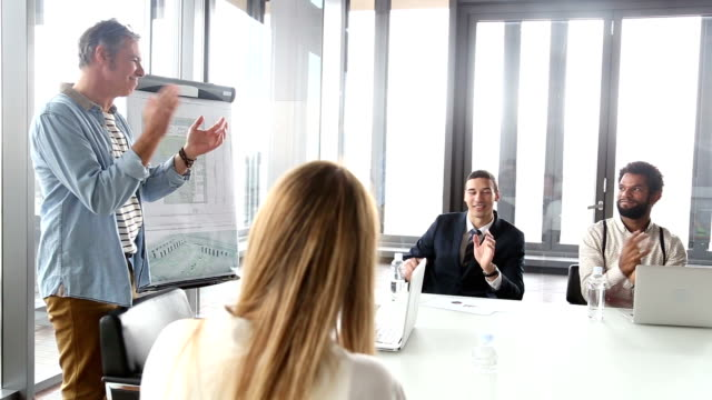 Side view of colleagues clapping on a meeting video