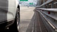 Side view of front wheel of vehicle standing on highway curb video