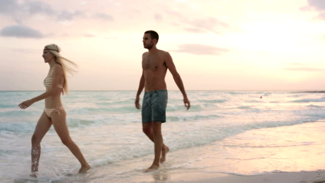 Side view of young man-woman couple in love enjoys and walks along ocean beach sea-side at sunrise or sunset in summer - gimbal steadicam HD video footage video