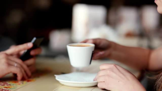 Side view of young woman drinking coffee. Woman has a cup of coffee. Hands of a man using his smartphone video
