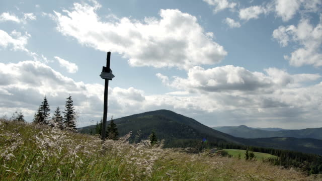 Signpost of hiking trails indicating the direction on the background of mountain peak and sky video