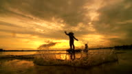 HD: Silhouette Asian fisherman on wooden boat casting a net for catching freshwater fish in nature river in the early morning before sunrise video