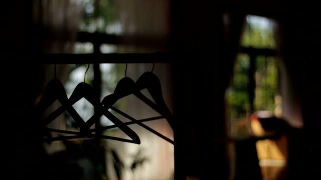 Silhouette coat hangers hanging on clothes rack video
