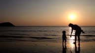 Silhouette daughter with mom playing and relaxing on beach video