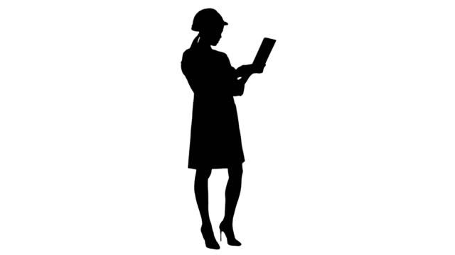 Silhouette Female engineer in helmet having video call via tablet video
