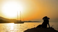 SUMMER CONCEPT, silhouette girl with straw hat watching sunset and boat at sea, wide shoot video