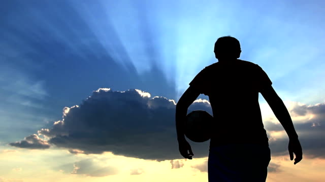 Silhouette man walks with a ball on a background of clouds at dawn at dusk video