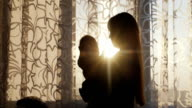 Silhouette mother with baby. Standing at the window at sunset, the sun's rays shine beautifully video