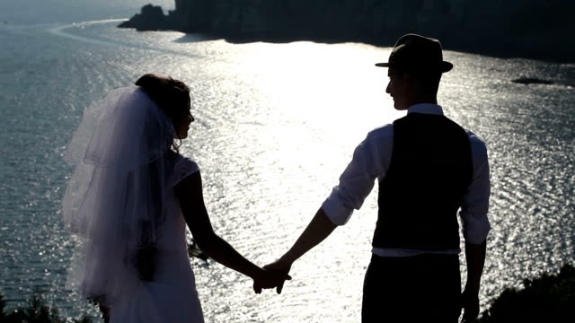 silhouette of a bride and groom on the background of the brilliant sea video