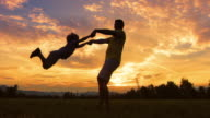 SLO MO DS Silhouette of a father spinning his son around outside at sunset video